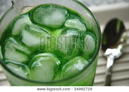 Lime drink and ice sits in a glass jug