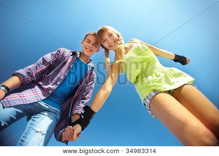 Portrait of two cheerful teenagers viewed from below against clear blue sky