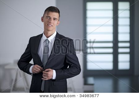 Businessman In Suit Poses Pulling His Suit Lapels