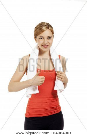 young smiling fitness woman with a white towel showing thumb up