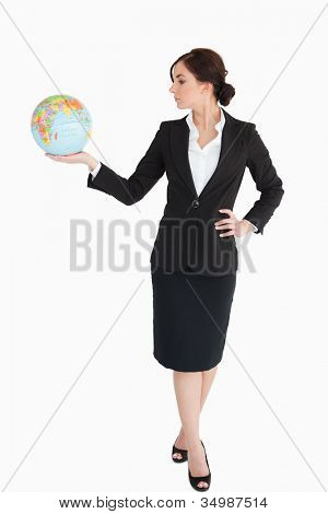 Attractive businesswoman holding an earth globe in her palm against white background