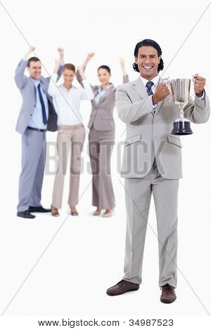Businessman smiling and holding a cup with people cheering behind him against white background