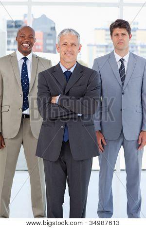 Diretor sorridente em pé na frente de um executivo descontraído e um funcionário sério