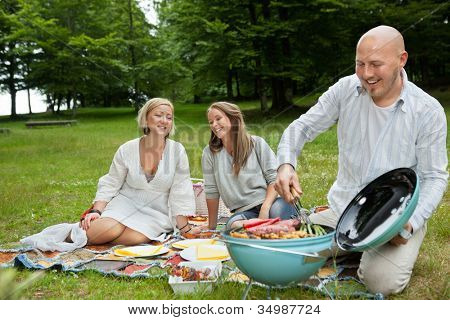 Happy Caucasian friends cooking barbeque meal at an outdoor picnic in forest park
