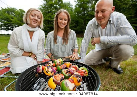 Three friends cooking shish kebabs over portable barbecue