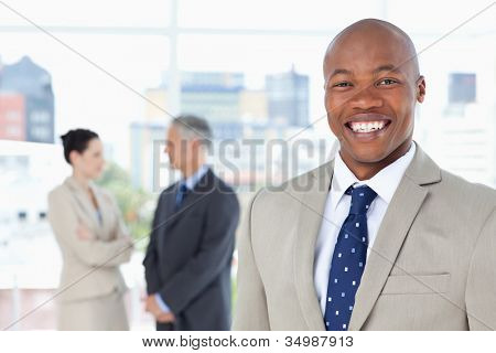 Young relaxed manager standing upright while showing a great smile
