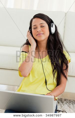 Close-up of a pretty Latin enjoying music on a laptop while sitting on the floor