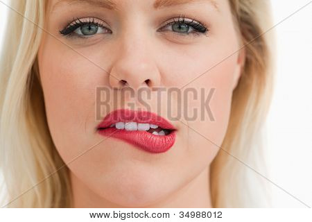 Attractive blonde woman biting her lips against a white background