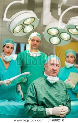 Surgeon sitting while crossing his hands with a team behind him in a surgical room