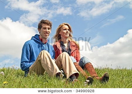 Young happy couple on the dyke in the countryside from the Netherlands
