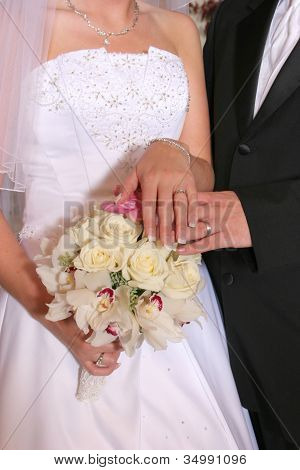 Bride and groom showing off rings