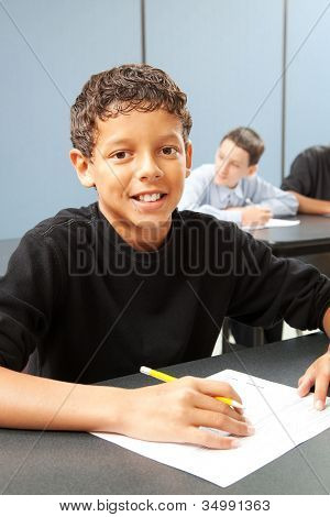 Handsome ethnic boy in school class.  Real person in real classroom.