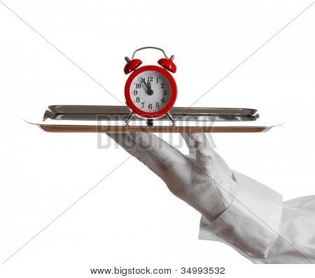 Hand in glove holding silver tray with alarm clock isolated on white