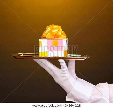 Hand in glove holding silver tray with giftbox on brown background