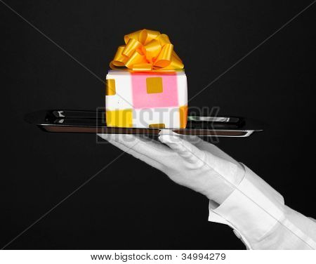 Hand in glove holding silver tray with giftbox isolated on black