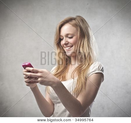Smiling beautiful young woman using a mobile phone
