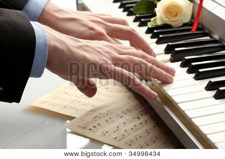 hands of man playing piano