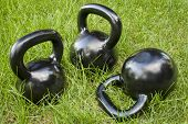 picture of kettlebell  - three heavy iron  kettlebells in green grass  - JPG