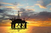 stock photo of oil rig  - Oil rig silhouette over orange sky  - JPG