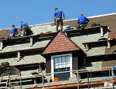 stock photo of shingle  - Workers on high roof are replacing old shingles - JPG