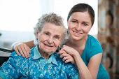 stock photo of responsible  - Senior woman with her caregiver at home - JPG