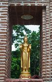 Golden Buddha Standing In A Brick Wall Frame  At The Entrance To The Temple Gate.