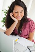 Smiling brunette student looking outside at her desk