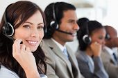 foto of telemarketing  - Smiling worker doing her job with a headset while looking at the camera - JPG
