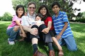 stock photo of mixed race  - Large multiracial family sitting on lawn in summer - JPG
