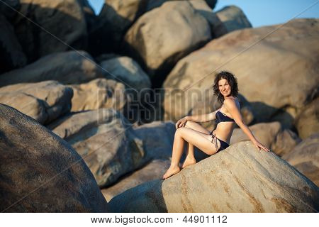 Woman In Swimsuit Takes Rest At Huge Rocks The Sea Shore