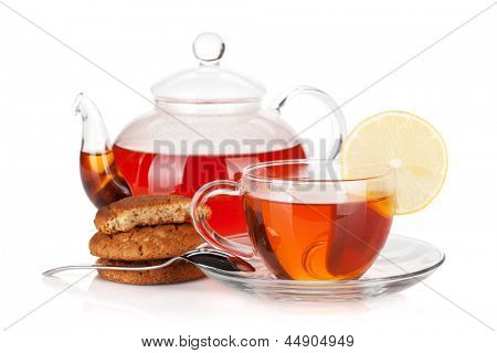 Glass cup and teapot of black tea with lemon and cookies. Isolated on white background
