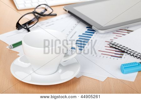 Coffee cup on contemporary workplace with financial papers, computer, glasses and office supplies