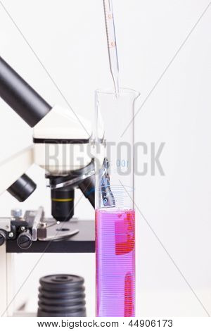 Lab technician working with equipment: microscope, test tubes  filled with colored fluid, chemical flasks