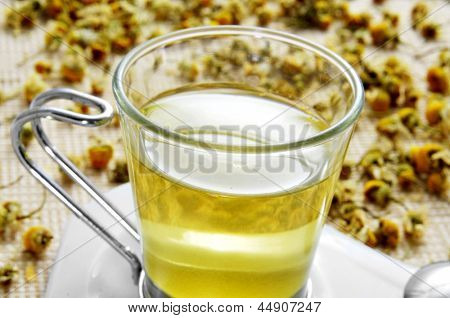 closeup of a glass cup with chamomile tea and a pile of dried chamomile flowers