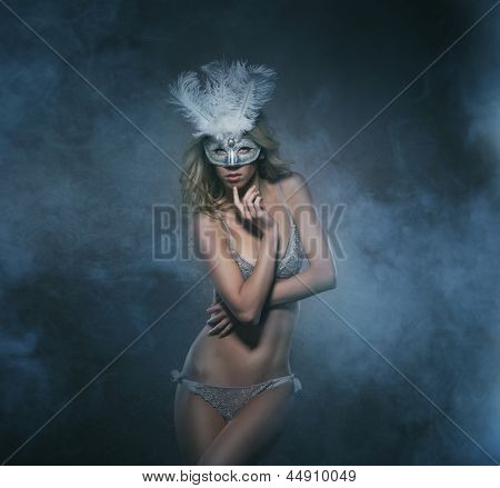 Beautiful and sexy striptease dancer over the smoky background