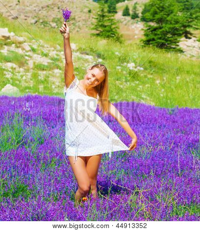 Pretty woman with lavender bouquet in hand dancing on purple flowers field, summer time holidays, leisure and freedom concept