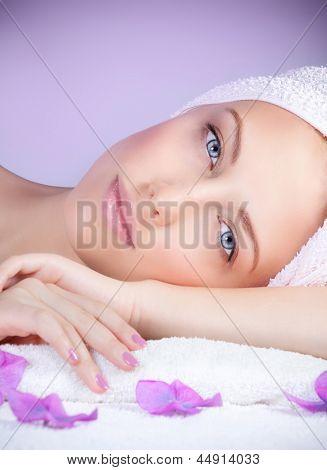 Closeup portrait of beautiful woman in spa salon laying down on massage table, enjoying dayspa, purple background, beauty treatment