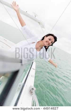 Excited woman in a yacht with open arms