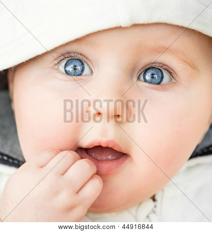 bright closeup portrait of adorable baby in the hood