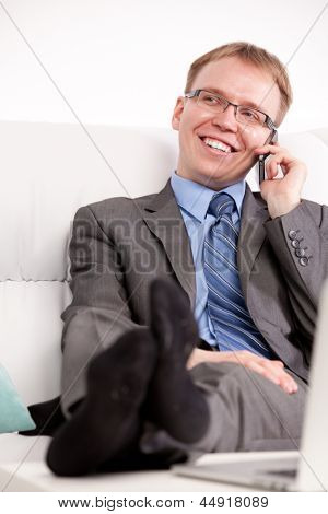 Young man speaking on the phone and sitting on sofa in living room