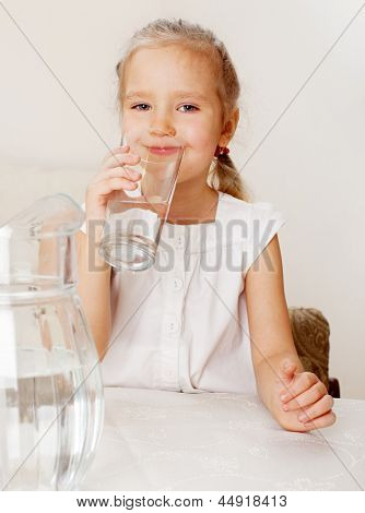 Child with glass pitcher water. Little girl drinking water at home