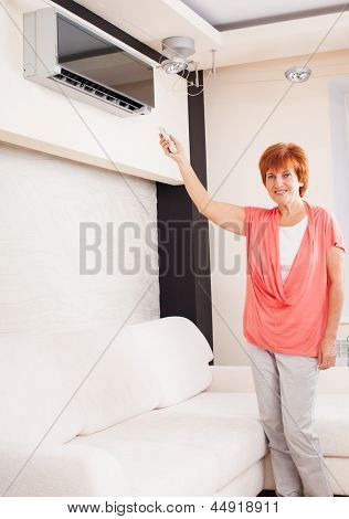 Woman holding a remote control air conditioner at home. Happy mature woman on sofa