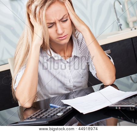 Sad woman looks at the bill. Female working at home