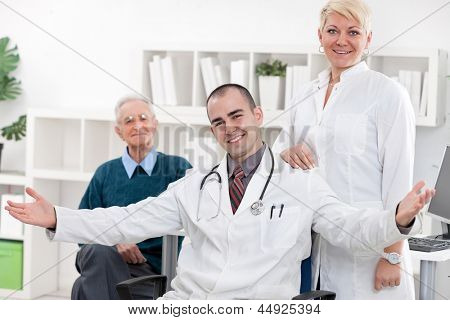 Young smiling doctor with nurse and patient at office
