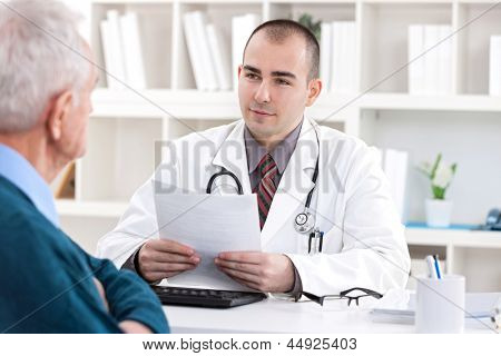 Male doctor talking with senior  patient at office