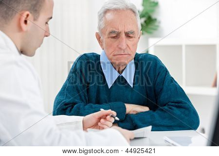 Young male doctor talking with senior patient
