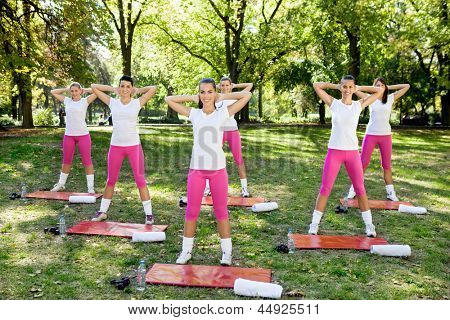 Group of women doing  warm up exercises at the park