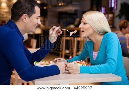 young men feeding his girlfriend, romantic lunch