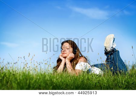 Young woman laying on grass listening to music