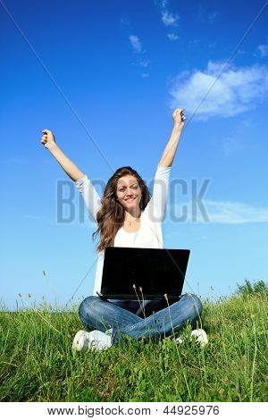 Happiness young  woman sitting on grass with laptop